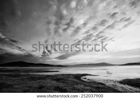 black and white high contrasted sky above the mountain lake - stock photo