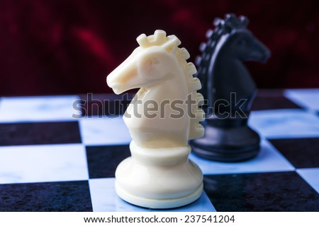 Black and white horses. Black and white chess pieces on blue board - stock photo