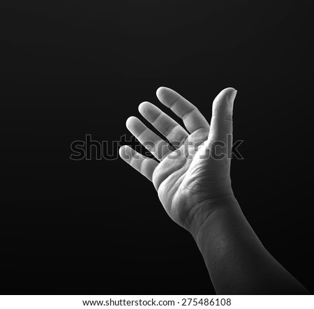 Black and white human open empty hand with palms up over black background.