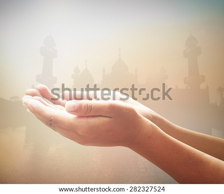 Black and white human open empty hands with palms up over blurred public mosque on sunset background. Eid Mawlid An Nabi, Milad Un Nabi, Prophet's Birthday, Muhammad, Muhammed, Mohammad concept. - stock photo