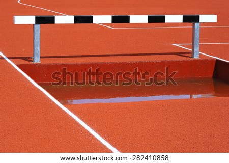 Black and white hurdles over water - stock photo