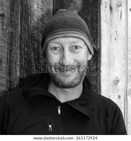 Black and white image of a bearded man wearing a cap. - stock photo