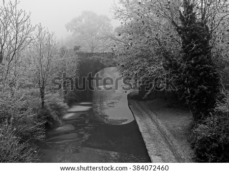 Black and White image of a Canal Bridge covered in frost on a cold and foggy Winters day - stock photo