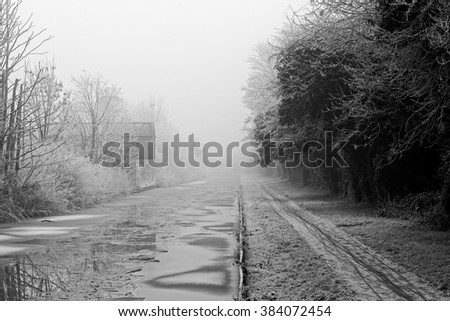 Black and White image of a canal building covered in frost on a cold and foggy Winters day - stock photo