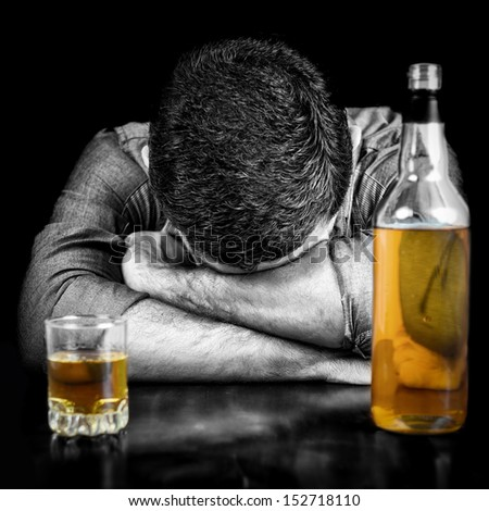 Black and white image of a drunk man sleeping with his head on a table and a bottle of whisky  (the bottle and glass have color) - stock photo