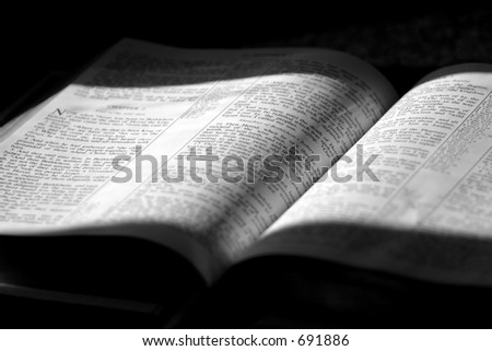 Black and White image of a family Bible in sunlight and shade, opened to Matthew Chapter 2 ~ The 3 wise men come to worship Jesus. - stock photo