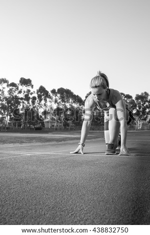 Black and white image of a female sprinter athlete getting ready to start a race on a tartan racetrack with dramatic lighting late in the afternoon, just before dusk - stock photo