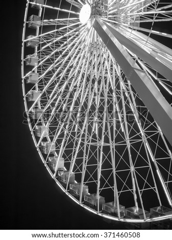 Black and white image of a Ferris wheel against a night sky