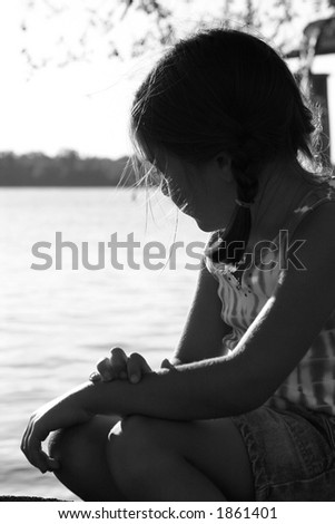 black and white image of a girl overlooking a lake - stock photo