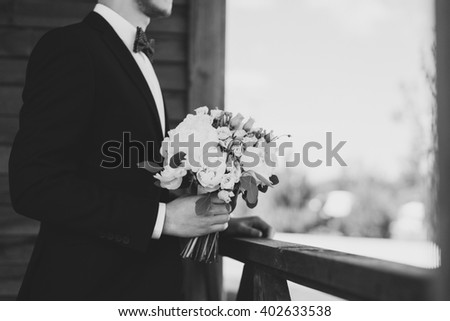 Black and white image of a groom with bouquet in his hands, waiting for the bride to come. - stock photo