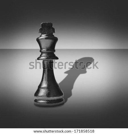 Black and white image of a king chess piece casting a shadow belonging to a pawn into a central highlight surrounded by vignetting - stock photo