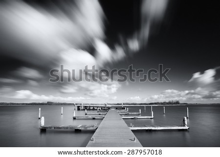 Black and white image of a lake and a jetty with clouds in the sky racing by with the wind and reflecting water - stock photo