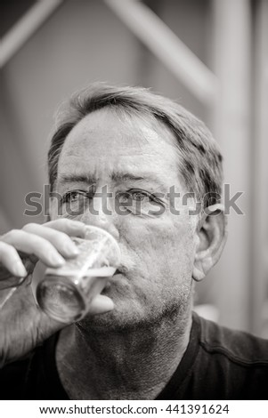 Black and white image of a man drinking a sample glass of beer