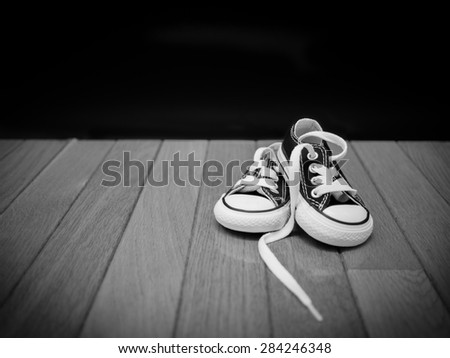 Black and white image of a pair of a small pair of sneakers on a wooden floor with a black background