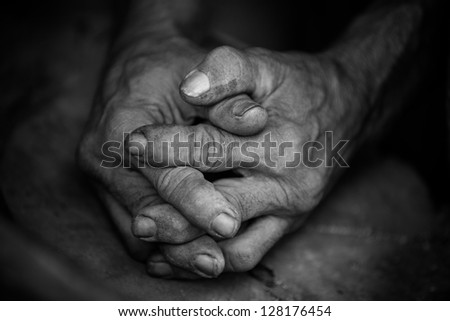 Black and white image of a pair of old hands clasped together