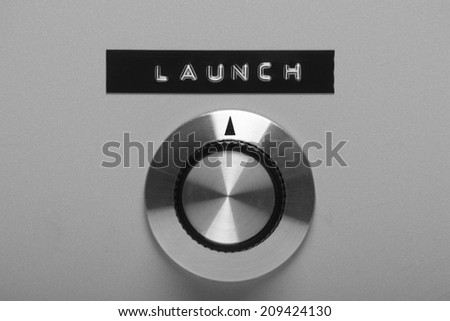 Black and white image of a retro style control switch on a metal panel, pointing at a printed label with the word Launch - stock photo