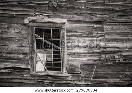 Black and white image of a weathered and weather damaged home and barn on the verge of collapse - stock photo