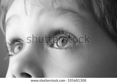Black and white image of a young child looking up. - stock photo