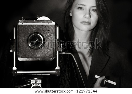 black and white image of a young woman taking a photography with a large 5x4 film camera - stock photo