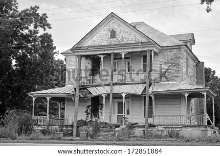 Black and white image of an abandoned weather beaten two story wooden American Colonial house supported with four by four boards to keep it from falling down.