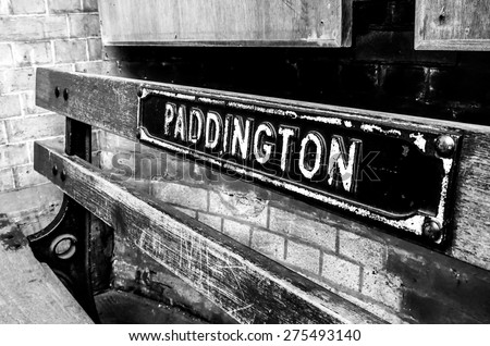 black and white image of an old bench at Paddington train station, London, UK - stock photo
