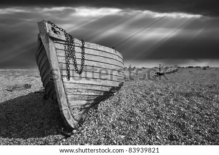 Black and white image of an old wooden fishing boat left to rot and decay on