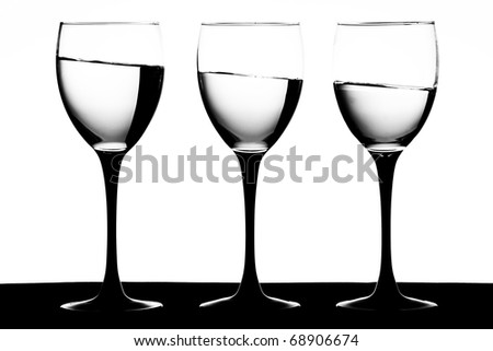 Black and white image of black stemmed wine glasses with wine on a slant