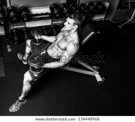Black and white image of bodybuilder who is having work out with dumbbells - stock photo