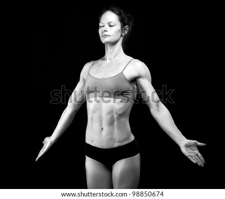 Black and white image of female athlete posing against black background. Some grain added. - stock photo