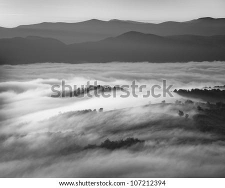 Black and white image of foggy mountains - stock photo