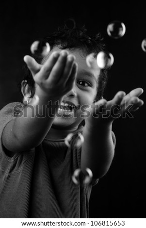 Black and white image of girl playing with bubbles