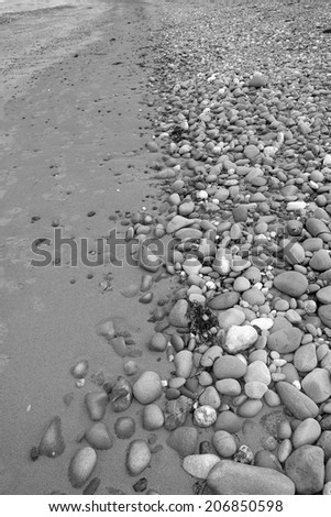 black and white image of grey pebbles and rocks in a beach on the wild atlantic way Ireland - stock photo