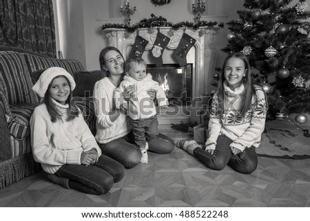 Black and white image of happy big family sitting on floor at fireplace on Christmas