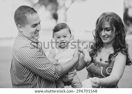 Black and white Image of happy family of three. Father, mother and little son playing outside in summer. Multi national family in park. Arabian daddy and European mom holding their child in hands. - stock photo