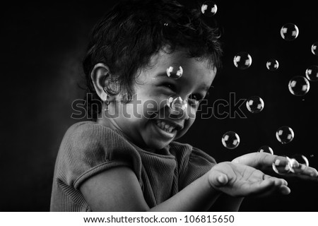 Black and white image of happy little girl playing with bubbles - stock photo
