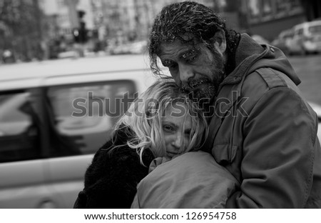 Black and white image of homeless couple embracing in city center - stock photo