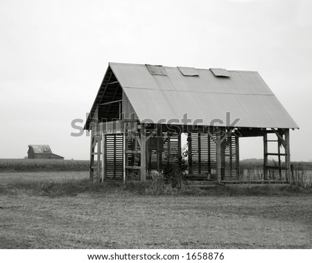 Black and white image of old farm building.  Cornfield and another old building in the background.