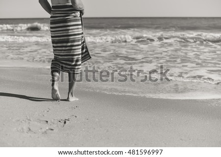 Black and white image of person walking by the shore in the beach, sunny outdoors sandy background