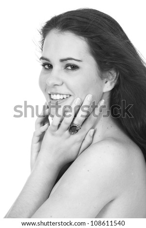 Black and white image of pretty brunette woman wearing white towel or boob tube with large ring jewelery on fingers posing on white background - stock photo