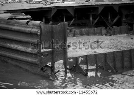 Black and white image of rusting ruins of what might have been a barge in a river bank.