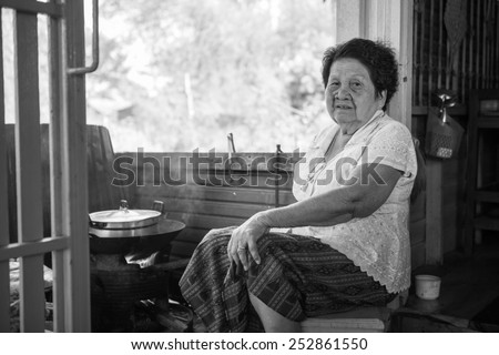 Black and white image of Senior asian woman cooking in kitchen - stock photo