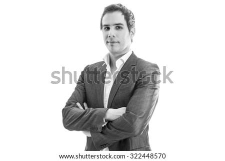 Black and white image of successful young businessman standing with his arms crossed looking confident towards you, with copy space ready for your text. - stock photo