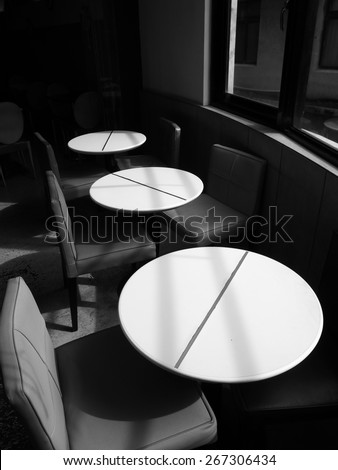 Black and white image of the interiors of a cafe. There are three white tables and six chairs by the window. Sun lights come in from the window and cast shadows on the desk and chairs.  - stock photo