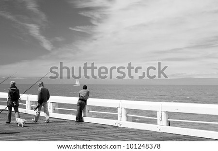 Black and white image of the pier, where people walking in Ostend. - stock photo