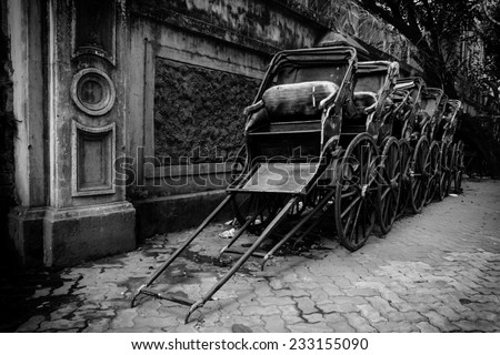 Black and white image of traditional hand pulled Indian rickshaws parked together in front of a old building in Kolkata