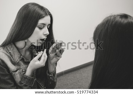 Black and white image of young woman applying makeup looking in hand mirror. Teenage girl doing daily morning routines. Teenager paints lips with a lipstick.