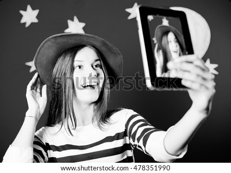 Black and white image of young woman trying on hat and making selfie. Happy girl excited on stars and moon wallpaper background.
