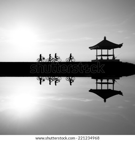 Black and white image Reflection of cyclists riding on a concrete barrier in bali indonesia Sanur beach at sunrise. This is a great place to visit when you are in Bali .. - stock photo