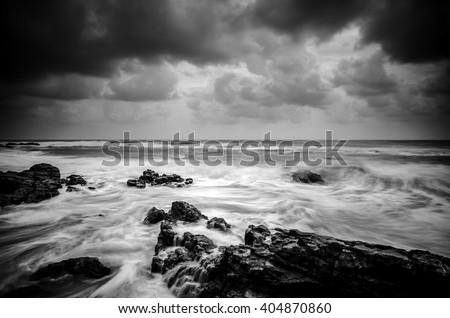 black and white image wave hitting the coastline with dramatic cloud background - stock photo