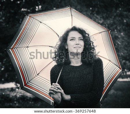 Black and white image with red shades of a woman holding umbrella  - stock photo
